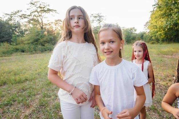 Grupa wesołych dziewczyn uśmiecha się i bawi w parku o zachodzie słońca. obóz letni dla dzieci.