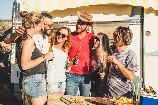 Grupa wesołych ludzi, młodzieńcy młodzieńcy bawią się razem w przyjaźni przy piwach