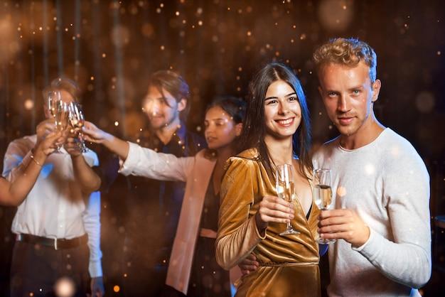 Grupa wesołych młodych ludzi ma imprezę i świętuje nowy rok w pomieszczeniu.