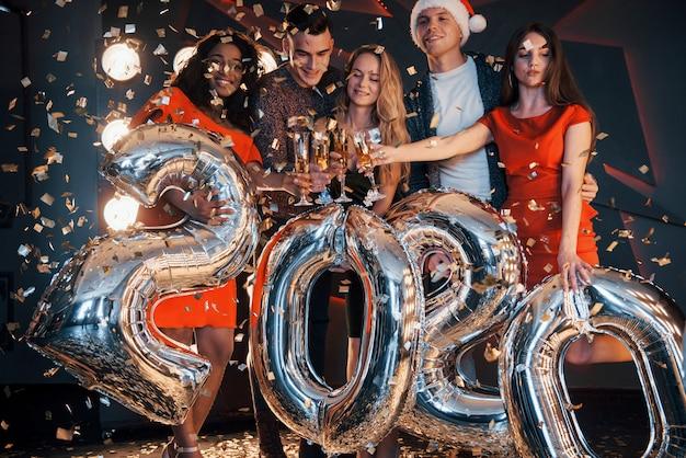 Grupa wesołych młodych pięknych wielonarodowych ludzi rzucających konfetti na imprezie. obchody 2020 roku.