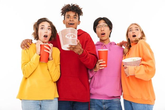 Grupa wesołych nastolatków na białym tle, oglądając film, jedząc popcorn
