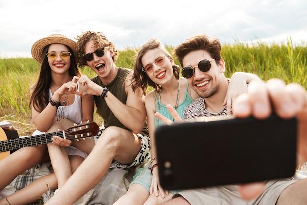 Grupa wesołych przyjaciół spędzających razem czas na świeżym powietrzu, pijąc piwo, grając na gitarze
