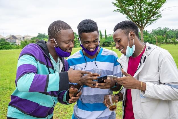 Grupa wesołych przyjaciół z maskami na twarz, którzy piją drinka i używają swoich telefonów w parku