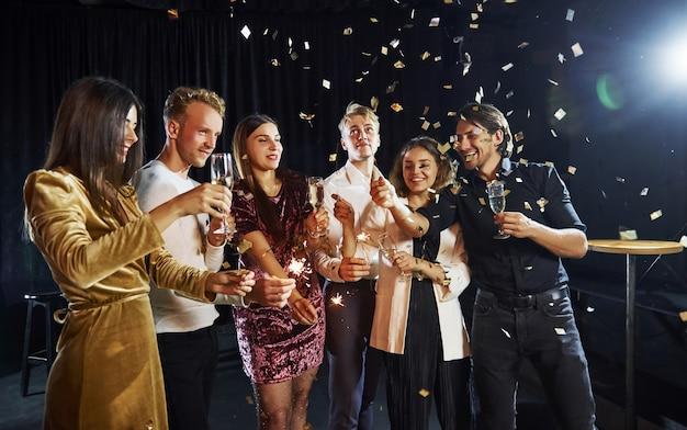 Grupa wesołych przyjaciół z okazji nowego roku w pomieszczeniu z napojami w rękach.