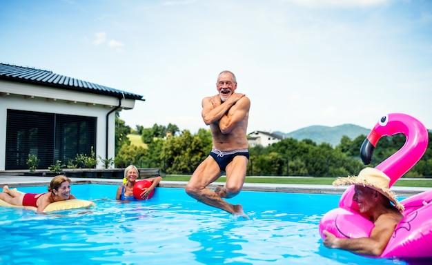 Grupa wesołych seniorów w basenie na zewnątrz na podwórku, skoki w wodzie.