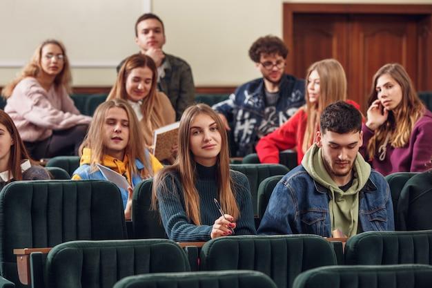 Grupa wesołych studentów siedząca w sali wykładowej przed lekcją.