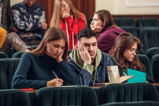 Grupa wesołych szczęśliwych studentów siedzących w sali wykładowej przed lekcją