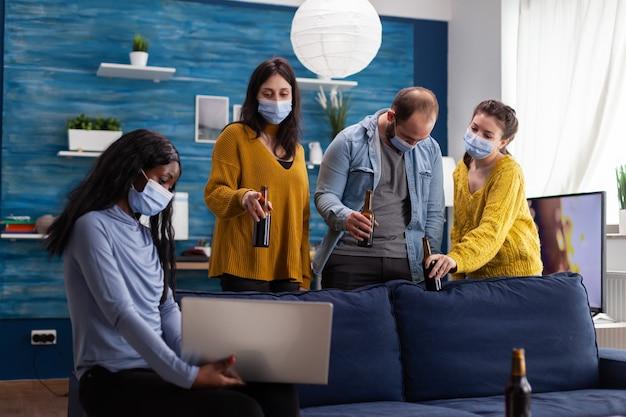 Grupa wesołych, szczęśliwych, wieloetnicznych przyjaciół, patrząc na zdjęcie na laptopie podczas wspólnej zabawy, rozmawiając, utrzymując dystans społeczny, nosząc maskę na twarz, pijąc piwo w salonie. obraz koncepcyjny.