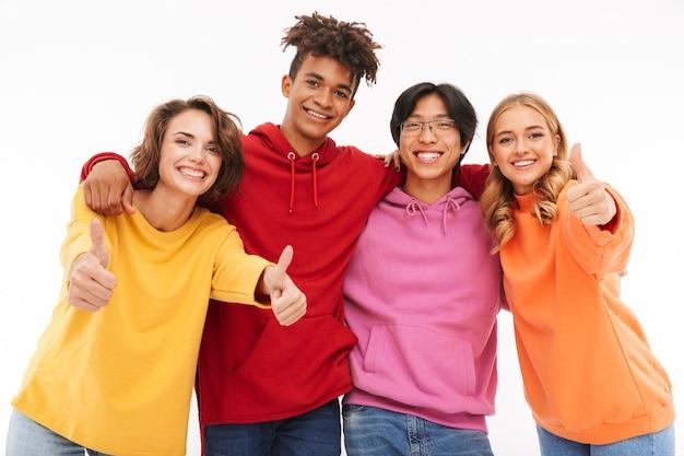 Grupa wesołych wielorasowych przyjaciół stojących na białym tle, dając kciuki do góry