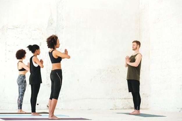 Grupa wieloetniczni ludzie stoi w joga studiu