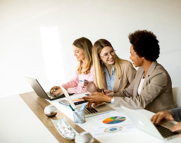 Grupa wieloetnicznych kobiet biznesu pracujących razem w biurze