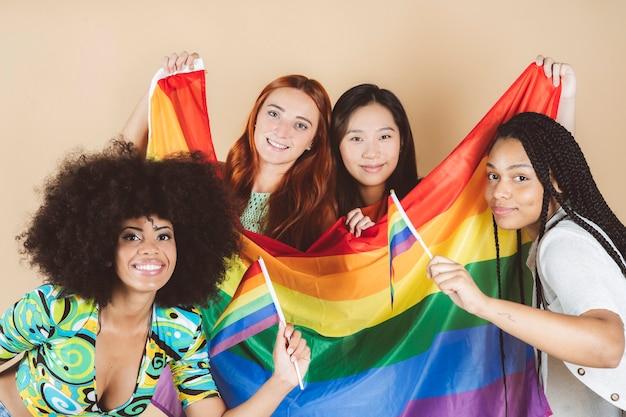 Grupa wieloetnicznych kobiet, które wznoszą flagę dumy gejowskiej, demonstrując w obronie praw lgbt