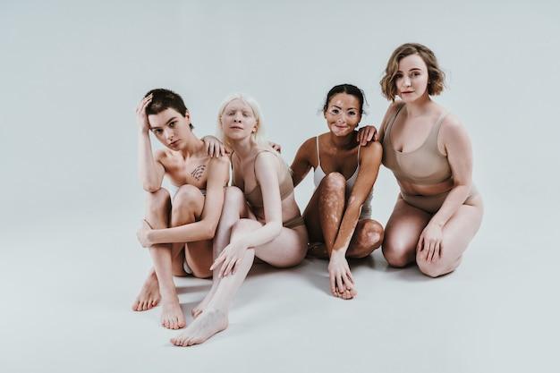 Grupa wieloetnicznych kobiet z różnym rodzajem skóry pozujących razem w studio pojęcie o ciele