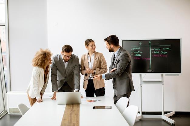 Grupa wieloetnicznych młodych ludzi biznesu pracujących razem w biurze
