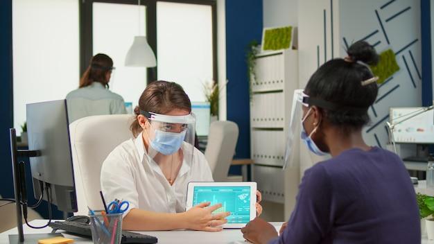 Grupa wieloetnicznych, pewnych siebie ludzi biznesu z maskami na twarz, analizujących dane za pomocą cyfrowego tabletu, siedząc w biurze z nową normą. koledzy pracujący w tle z poszanowaniem dystansu społecznego
