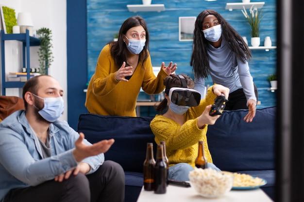 Grupa wieloetnicznych przyjaciół bawiących się grając w gry wideo za pomocą zestawu słuchawkowego wirtualnej rzeczywistości i joysticka w masce na twarz, zachowując dystans społeczny, aby uniknąć rozprzestrzeniania się koronawirusa. obraz koncepcyjny.