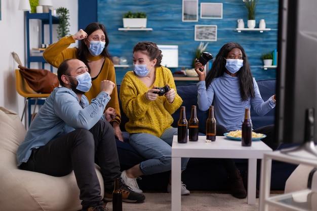 Grupa wieloetnicznych przyjaciół świętujących zwycięstwo podczas grania w gry wideo z joypadem w salonie, utrzymujący dystans społeczny w maskach na twarz podczas globalnej pandemii. ludzie cieszący się czasem spędzonym razem.
