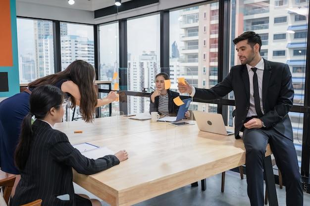 Grupa wieloetnicznych współpracowników biznesowych burzy mózgów na temat pomysłu na biznes z karteczką na pokładzie w nowoczesnym biurze