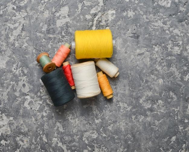 Grupa wielokolorowe motkach nici na szarym tle betonu. pojęcie robótek ręcznych. wykonane ręcznie do szycia ubrań.