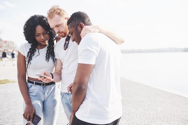 Grupa wielorasowe szczęśliwych przyjaciół za pomocą gadżetu na zewnątrz. pojęcie szczęścia i przyjaźni wieloetnicznej razem przeciwko rasizmowi