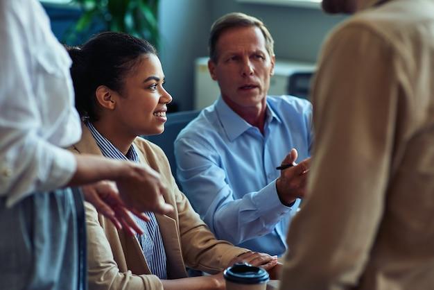 Grupa wielorasowych ludzi biznesu spotykająca się w nowoczesnej przestrzeni biurowej lub coworkingowej