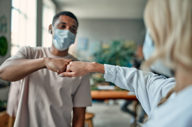 Grupa wielorasowych ludzi pracujących w nowoczesnym biurze podczas koronawirusa. młodzi ludzie biznesu i starszy szef pracują razem, nosząc maski ochronne na twarz. środki zapobiegawcze podczas covid-19