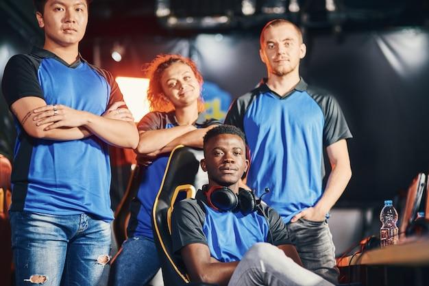 Grupa wielorasowych profesjonalnych graczy cybersportowych patrzących w kamerę i uśmiechających się uczestniczących w