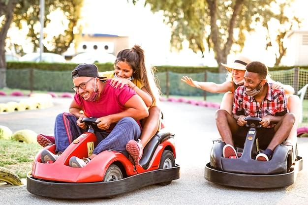 Grupa wielorasowych przyjaciół bawiących się gokartem - młodzi ludzie z maską na twarzy uśmiechnięci i weseli podczas wyścigów mini - pary na dworze w podwójnej randce - nowy styl życia