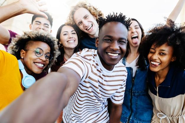 Grupa wielorasowych szczęśliwych najlepszych przyjaciół robi zdjęcie selfie za pomocą aparatu w smartfonie