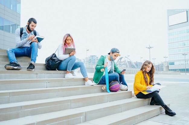 Grupa wielorasowych uczniów w ochronnych maskach uczy się siedząc na schodach w społecznej odległości poza uczelnią - szczęśliwi przyjaciele w czasach koronawirusa wykonują prace szkolne poza szkołą
