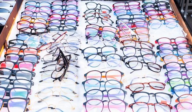 Grupa wielu kolorowych okularów w rzędach, wybór okularów w sklepie optycznym