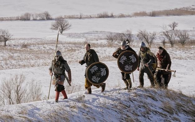 Grupa wikingów z tarczami i mieczami idąca naprzód na łące. rekonstrukcja średniowieczna.