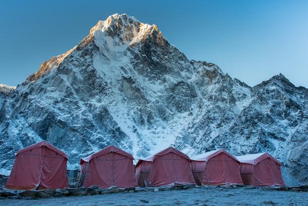 Grupa wspinaczy jasnych namiotów na lodowcu khumbu w obozie podstawowym everest z kolorowym pr