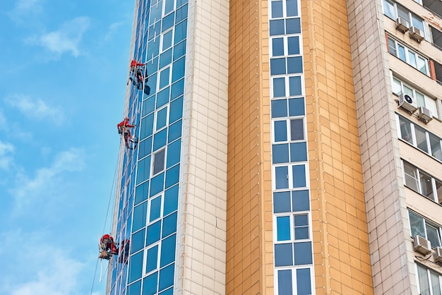 Grupa wspinaczy przemysłowych pracuje nad nowoczesnym budynkiem na zewnątrz