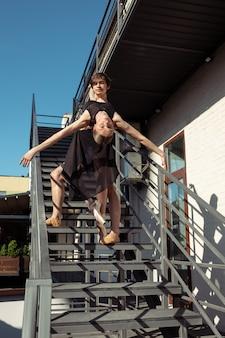 Grupa współczesnych tancerzy baletowych występująca na schodach miasta
