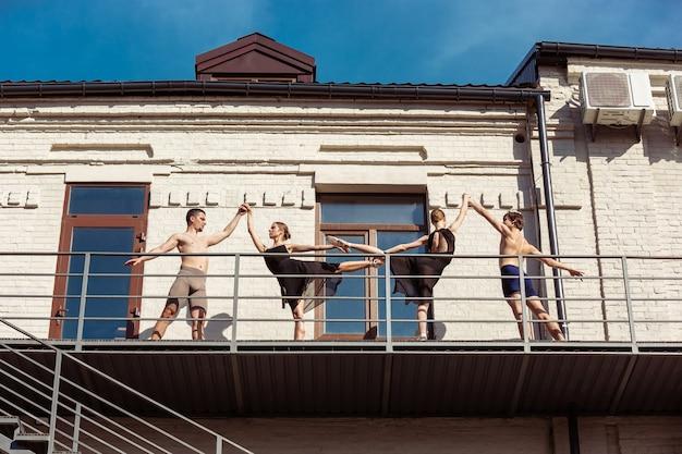 Grupa współczesnych tancerzy baletowych występująca na schodach w mieście.