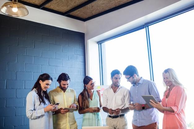 Grupa współpracowników korzystających z laptopów i smartfonów