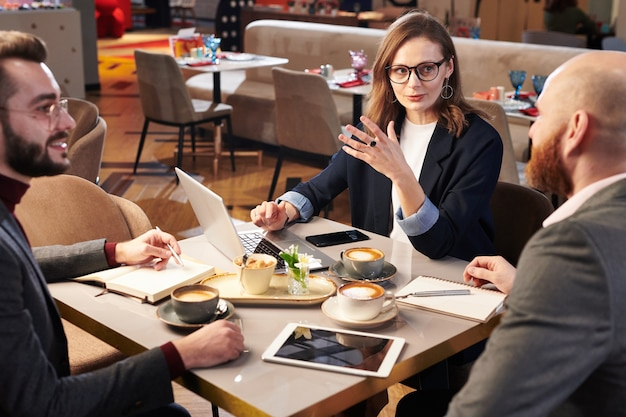 Grupa współpracowników siedzi przy stole z filiżankami do kawy w kawiarni i omawiając pomysły biznesowe za pomocą urządzeń przenośnych