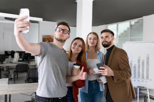 Grupa współpracowników w biurze robiących selfie