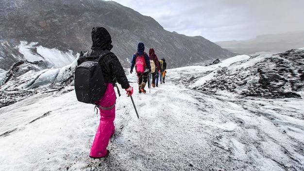 Grupa wycieczkowicza spacer na lodowu podczas śniegu na solheimajokull