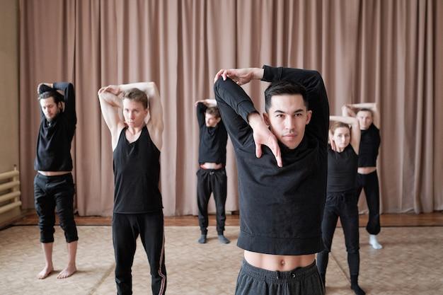 Grupa wysportowanych chłopaków i dziewcząt w czarnych t-shirtach i spodniach ćwiczy jedno z ćwiczeń tanecznych, powtarzając za swoim instruktorem