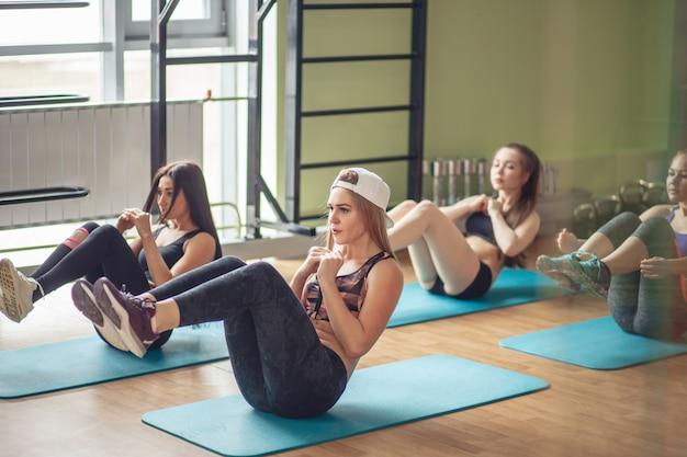 Grupa wysportowanych dorosłych mężczyzn i kobiet wykonujących ćwiczenia w pozycji siedzącej, aby wzmocnić swoje podstawowe mięśnie brzucha podczas treningu fitness