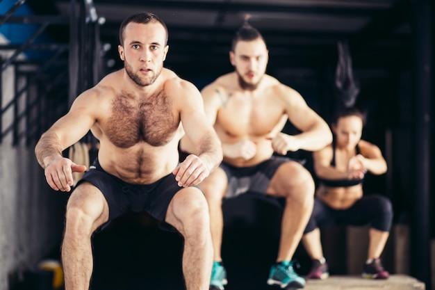 Grupa wysportowanych ludzi przeskakuje nad niektórymi skrzyniami w siłowni