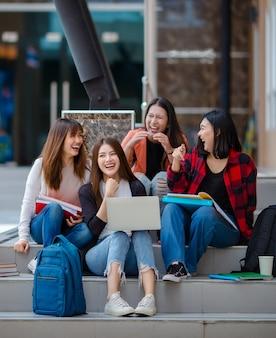 Grupa zachwyconych azjatyckich studentek zbierających się na schodach w kampusie uniwersyteckim i odrabiających wspólnie pracę domową podczas korzystania z laptopa. pomysł na bliskiego przyjaciela życia nastolatków.