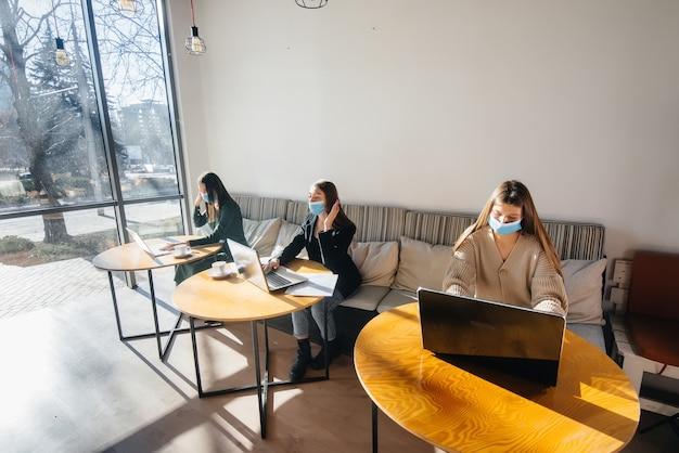 Grupa zamaskowanych dziewczyn podczas pracy na laptopie w kawiarni zachowuje dystans towarzyski.