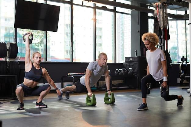Grupa zdrowych ludzi trenujących ze sprzętem sportowym w nowoczesnej siłowni