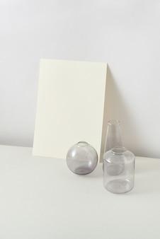 Grupa ze szklanych wazonów o różnych kształtach i pionowo stojącej kartce papieru rzemieślniczego na jasnym stole na pastelowym szarym tle, kopia przestrzeń. koncepcja naturalnego eko.