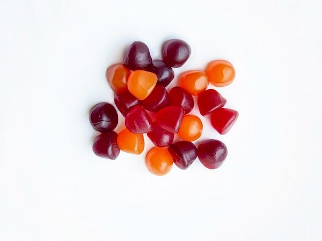 Grupa żelków multiwitaminowy czerwony, pomarańczowy i fioletowy na białym tle. pojęcie zdrowego stylu życia.