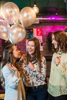 Grupa żeńscy przyjaciele ma zabawę w przyjęciu przy noc klubem