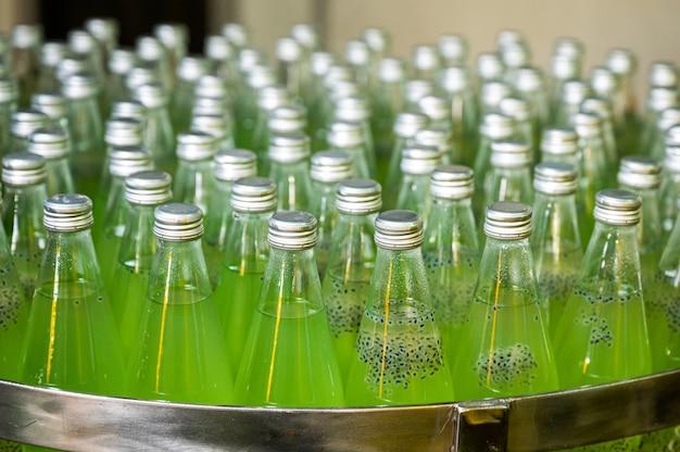 Grupa zielonego soku w butelkach szklanych na przenośniku stalowym linii produkcyjnej w zakładzie przetwórstwa napojów